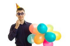 Le jeune type gai garde près des verres de papier d'oeil et des un bon nombre de boules colorées Photographie stock