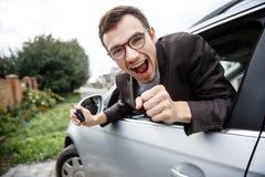 Le jeune type hanté jette un coup d'oeil de la fenêtre de voiture tout en regardant la caméra Il tient les clés à sa main droite  photographie stock libre de droits