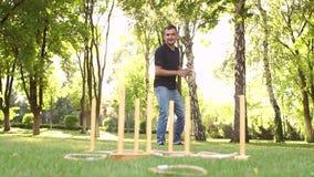 Le jeune type joue un jeu de lancer d'anneau en parc banque de vidéos