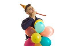 Le jeune type mignon regardant en direction du soufflement et maintient un bon nombre de boules multicolores disponibles Photographie stock libre de droits