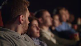 Le jeune type obtiennent effrayé tout en observant le film d'horreur Film effrayant au cinéma banque de vidéos