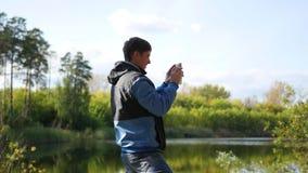 Le jeune type prend des photos du paysage d'automne au téléphone banque de vidéos