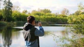 Le jeune type prend des photos du paysage d'automne au téléphone clips vidéos