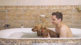 Le jeune type prend un bain chaud avec son chien banque de vidéos