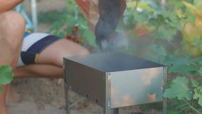 Le jeune type remplit charbons dans le brasero banque de vidéos