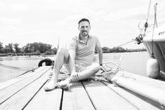 Le jeune type s'assied dans le polo bleu sur le pilier près du yacht homme bel de touristes souri détendant et appréciant la vue photo libre de droits