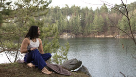 Le jeune type s'assied sur la haute banque au-dessus du lac Photographie stock libre de droits