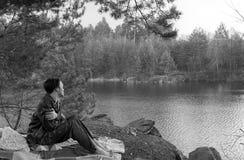 Le jeune type s'assied sur le rivage de lac pendant le début de la matinée Photo stock