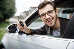Le jeune type satisfait jette un coup d'oeil de la fenêtre de voiture tout en regardant la caméra Il tient les clés à sa main dro images stock