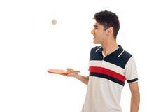 Le jeune type se tient latéral et tenant des raquettes de tennis Photos libres de droits