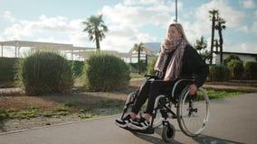 Le jeune utilisateur de fauteuil roulant féminin heureux marche en parc dans le jour ensoleillé banque de vidéos