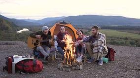 Le jeune voyageur de type joue la guitare, ses amis font cuire des saucisses sur le feu au coucher du soleil en montagnes Amitié banque de vidéos