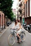 Le jeune voyageur féminin de sourire heureux avec la bicyclette et le papier tracent au centre de la ville de Barcelone Déplaceme image libre de droits