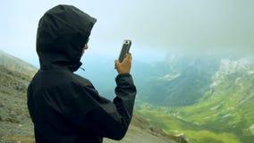 Le jeune voyageur utilisent le téléphone de Smart à la crête de montagne banque de vidéos
