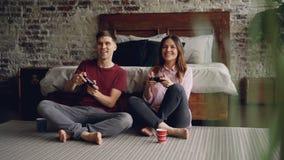 Le jeunes ami et amie mignons de couples jouent le jeu vidéo tenant des manettes se reposant sur le plancher de chambre à coucher banque de vidéos