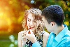 Le jeunes garçon et fille mangent des cerises Le concept est amour, mode de vie Photographie stock