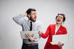 Le jeunes homme d'affaires et femme d'affaires avec des ordinateurs portables communiquant sur le fond gris Photographie stock