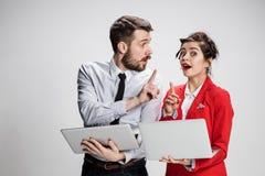 Le jeunes homme d'affaires et femme d'affaires avec des ordinateurs portables communiquant sur le fond gris Photo stock