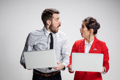 Le jeunes homme d'affaires et femme d'affaires avec des ordinateurs portables communiquant sur le fond gris Image libre de droits