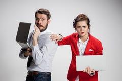 Le jeunes homme d'affaires et femme d'affaires avec des ordinateurs portables communiquant sur le fond gris Images libres de droits