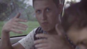 Le jeunes homme et femme caicasian s'asseyent dans la voiture le jour nuageux d'été clips vidéos