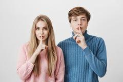 Le jeunes homme et femme européens émotifs avec les cheveux blonds se sont habillés dans des chandails roses et bleus tenant des  Photographie stock