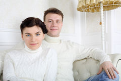 Le jeunes mari et épouse de sourire dans des chandails blancs s'asseyent sur le sofa Image libre de droits