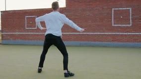 Le jeunes type, danseur caucasiens mignons de rue, dans le pantalon noir de denim et le chandail blanc, exécute une série de da banque de vidéos