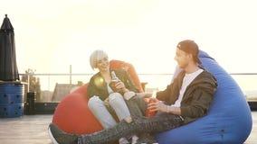 Le jeunes type et fille s'asseyent dans des fauteuils multicolores dans la boisson potable d'énergie de café de terrasse Les amis banque de vidéos