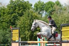 Le jockey saute par-dessus un obstacle Photographie stock libre de droits