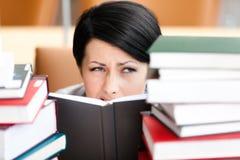 Le joli étudiant féminin regarde à l'extérieur au-dessus du livre photos stock