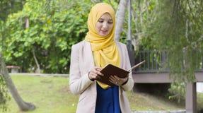 Le joli étudiant universitaire ont plaisir à lire en parc Photographie stock