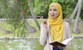 Le joli étudiant universitaire ont plaisir à lire et penser en parc Photographie stock libre de droits