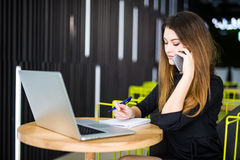 Le joli directeur heureux parlant au téléphone portable avec le client et écrivent des notes dans le bureau moderne image stock