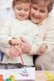 Le joli grand-parent enseigne l'enfant à peindre Photographie stock