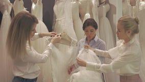 Le joli groupe de sourire de jeunes mariées choisit la robe blanche à la boutique de la mode de mariage banque de vidéos