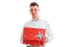 Le joli homme d'élégance dans la chemise blanche ouvrent un boîte-cadeau et le sourire sur l'appareil-photo Photographie stock