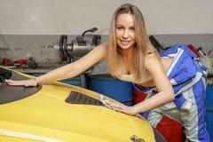 Le joli mécanicien de fille polit le capot de voiture photo stock