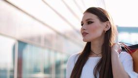 Le joli mannequin dans la robe blanche pose avec des paniers avant un bâtiment en verre moderne clips vidéos