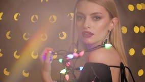 Le joli mannequin joue avec la guirlande électrique à l'arrière-plan de bokeh de lumières jaunes, mouvement lent banque de vidéos