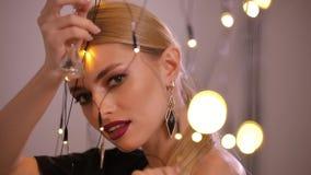 Le joli mannequin joue avec la guirlande électrique, mouvement lent banque de vidéos