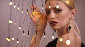 Le joli mannequin joue avec la guirlande électrique, mouvement lent clips vidéos
