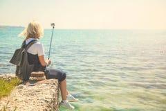 Le joli portrait de selfie de prises de touriste de jeune femme au bord de la mer sur une fille de jour ensoleillé prend la photo Images stock