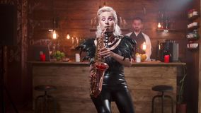 Le joli saxophoniste féminin avec lumineux composent exécute dans un café de jazz clips vidéos