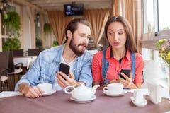 Le jolis homme et femme utilisent des téléphones est Photographie stock