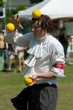 Le jongleur équilibre la bille sur la tête au festival photos stock