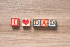 Le jouet bloque le PAPA d'AMOUR de l'orthographe I sur un fond en bois Photo stock