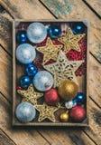 Le jouet d'arbre de Noël se tient le premier rôle, les boules et la guirlande dans la boîte en bois Photographie stock