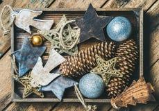 Le jouet d'arbre de Noël se tient le premier rôle, les boules et la guirlande dans la boîte en bois Photo libre de droits