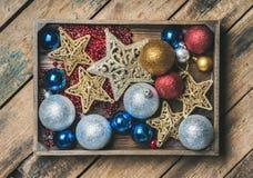 Le jouet d'arbre de Noël se tient le premier rôle, les boules et la guirlande dans la boîte en bois Images libres de droits